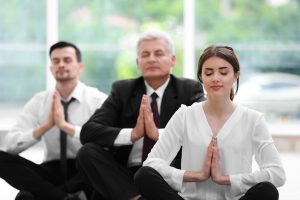 Tame Your Triggers. Business people relaxing in meditation pose in office